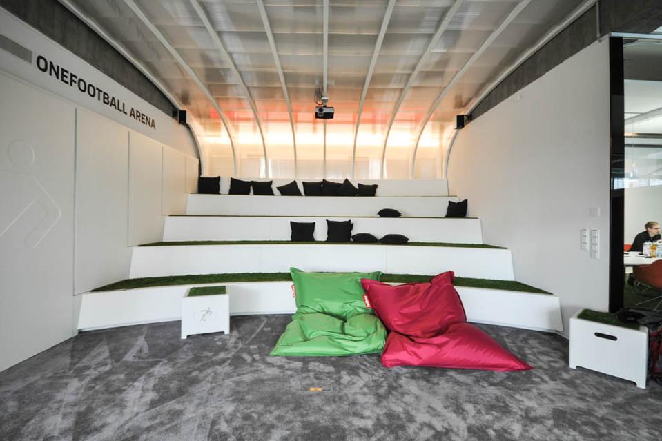 In einer Arena können die Angestellten Fußballspiele auf einer Leinwand sehen, es gibt Tore, um in den Pausen ein wenig zu trainieren, und natürlich ist auch der Teppich in den Büros grasgrün – genau wie die Sitzflächen auf den Hockern.