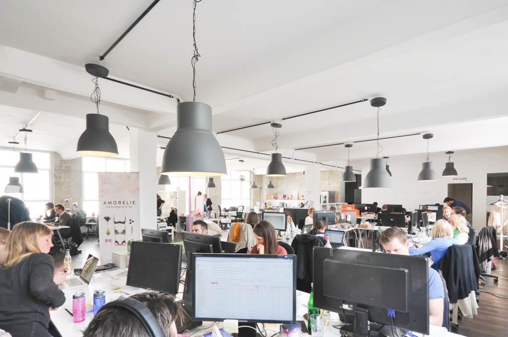 An mehreren großen Tischen sitzen die überwiegend jungen Mitarbeiter zusammen. Sie stellen neue Produkte online, telefonieren oder chatten mit Kunden und drehen ein paar Runden an der Stange, die in der Mitte des Büros aufgebaut ist.